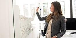 woman-wearing-gray-blazer-writing-on-board-260px